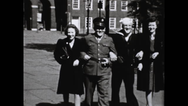 two couples walk arm in arm; looks at the map together; one man wears a sailor uniform while the other wears a soldier uniform - independence hall stock videos & royalty-free footage
