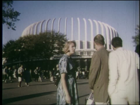 view two couples walk toward unusual pavilion at ny world's fair - 1964年点の映像素材/bロール