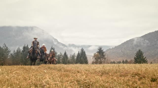 stockvideo's en b-roll-footage met slo mo twee cowboys en cowgirl galopperen over een weiland - kleine groep dieren