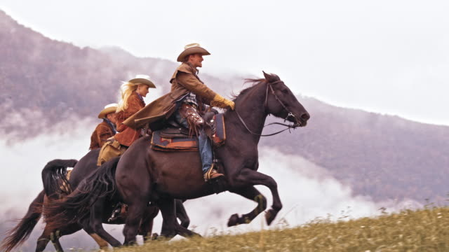 slo mo ds two cowboys and cowgirl riding galloping horses - cowboy stock videos and b-roll footage