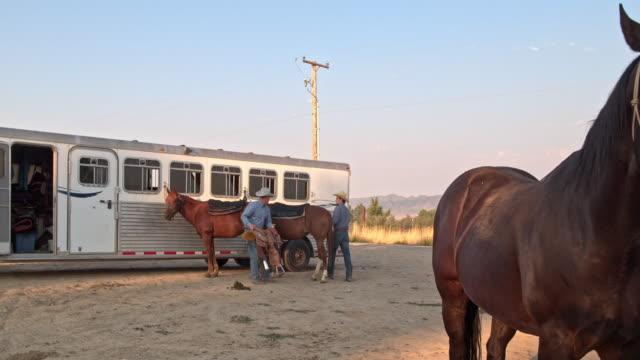 Two cowboys preparing their horses to horseback riding in Utah, USA