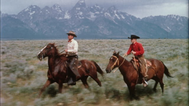 two cowboys ride horses across the plains with the tetons in the background. - カウボーイ点の映像素材/bロール