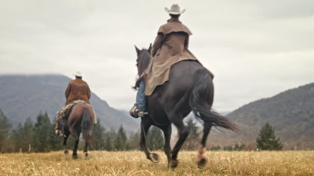 SLO MO Two cowboys riding horses in the mountains