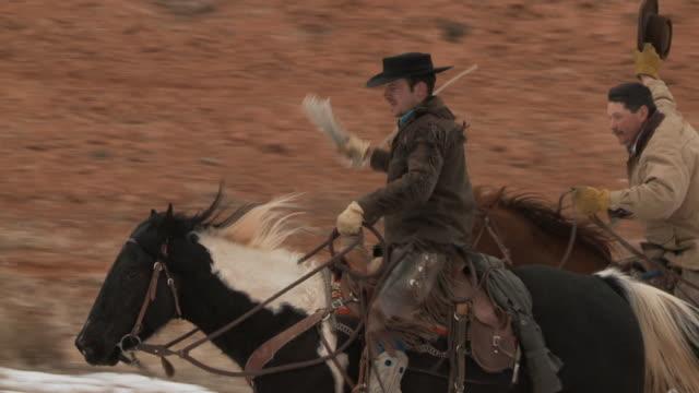 vidéos et rushes de slo mo ms pan two cowboys riding horses / shell, wyoming, usa - petit groupe d'animaux