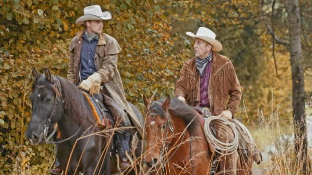 Två cowboys talar medan ridning sina hästar