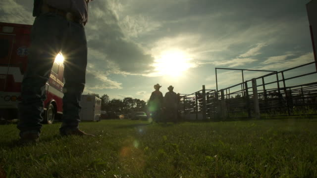 two cowboys walk in backlit in a rodeo stadium - badlands stock videos & royalty-free footage