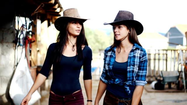 Två cowgirl systrar är inspektion sitt stall