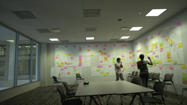 vídeos de stock e filmes b-roll de ws tu two coworkers brainstorm in creative conference room, chicago, illinois, usa - mesa de reunião