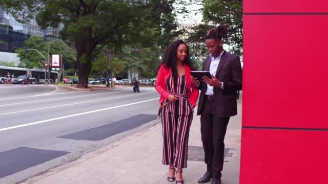 Zwei Coworker diskutieren und nutzen digitales Tablet auf der Straße