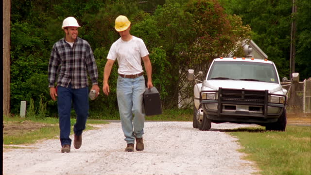 Two coworkers in hardhats walk together on a dirt road.