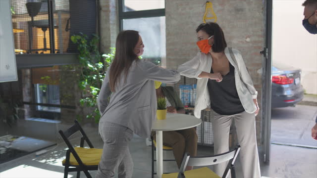two coworkers with face masks performing elbow bump with female colleagues after arrival in office - arrival stock videos & royalty-free footage