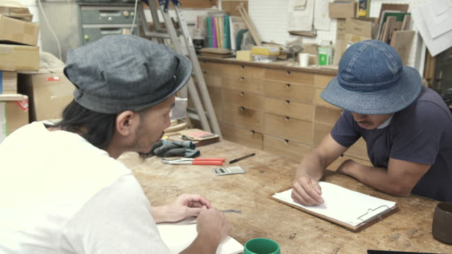 Two craftsmen are meeting in their studio