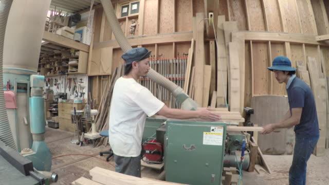 Two craftsmen use automatic sander machine