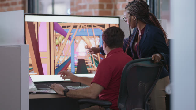 two creative designers examine and discuss a 3d illustration on digital display monitor - leadership illustration stock videos & royalty-free footage