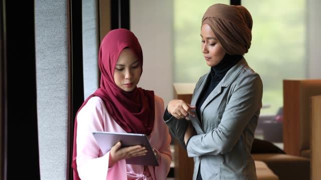 zwei kreative junge muslimische frauen diskutieren ideen im modernen büro - erwachsener über 30 stock-videos und b-roll-filmmaterial