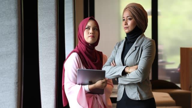 zwei kreative junge muslimische frauen diskutieren ideen im modernen büro - coworking space stock-videos und b-roll-filmmaterial
