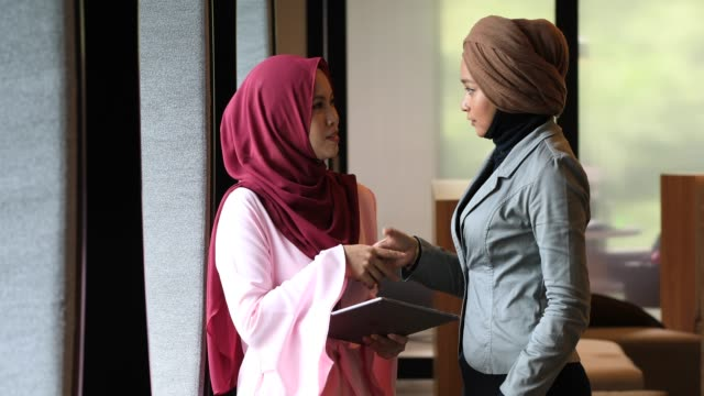 two creative young muslim women shaking hands in modern office - malaysian ethnicity stock videos and b-roll footage
