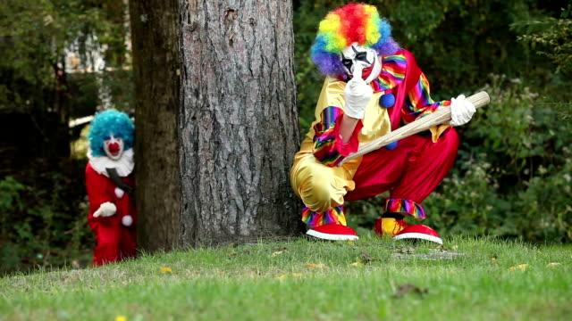 zwei gruselige clowns versteckt in wäldern - bedrohung und belästigung stock-videos und b-roll-filmmaterial