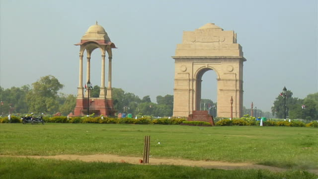 ws, two cricket players, india gate in background, new delhi, india - cricket video stock e b–roll