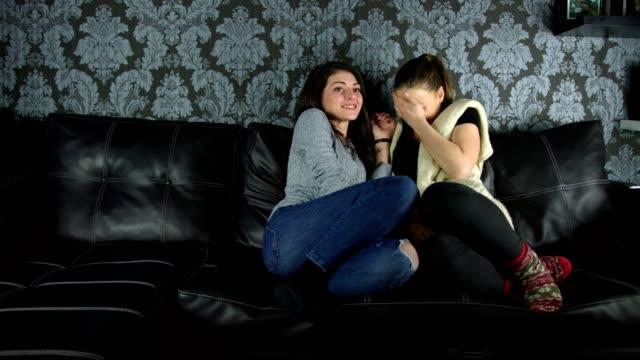 Deux jolies filles se fait vraiment peur en regardant un film d'horreur