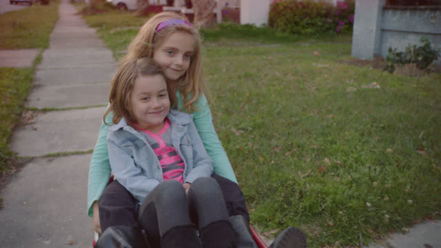 vidéos et rushes de ms slo mo. two cute girls ride in little red wagon down neighborhood sidewalk. - chariots et charrettes