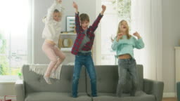 Two Cute Little Girls and Young Adorable Boy Have Fun, Jumping High on a Couch at Home. Happy Children Playing in the Sunny Living Room. In Slow Motion.