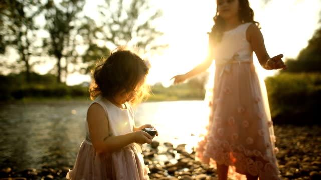 二人のかわいい姉妹。夕暮れ川 - 石点の映像素材/bロール