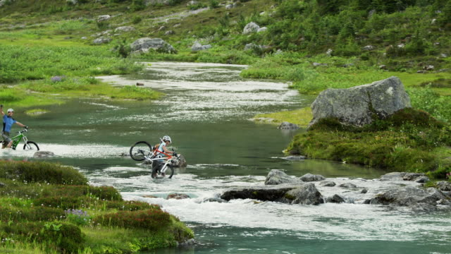 WS TD Two cyclists crossing Alpine river, carrying mountain bikes, Coast Mountains, Squamish, British Columbia, Canada