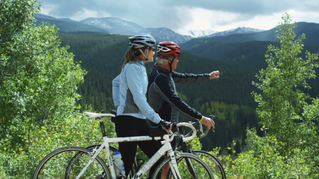 two cyclists looking out across a mountain view - denver stock videos and b-roll footage