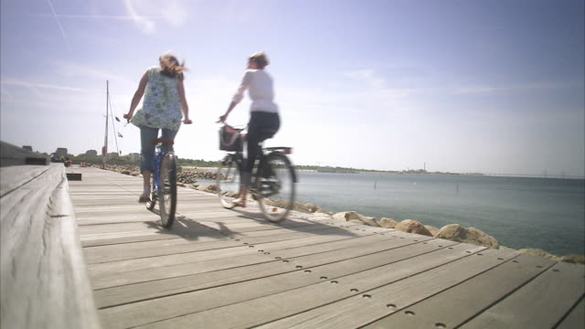 Two cyclists passing by Malmo Skane Sweden.
