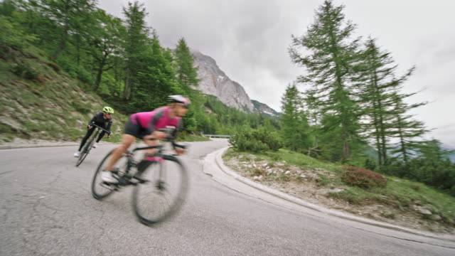 two cyclists speeding down the mountain road on their road  bikes - t shirt stock videos & royalty-free footage