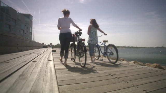 Two cyclists walking by Malmo Skane Sweden.