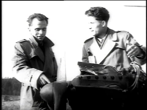 vidéos et rushes de two czech amateur pilots walking around and inspecting a crashed plane in a field after stealing it and flying to their freedom / bavaria germany - 1953