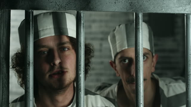two dangerous prisoners looking through the prison bars - security bar stock videos and b-roll footage