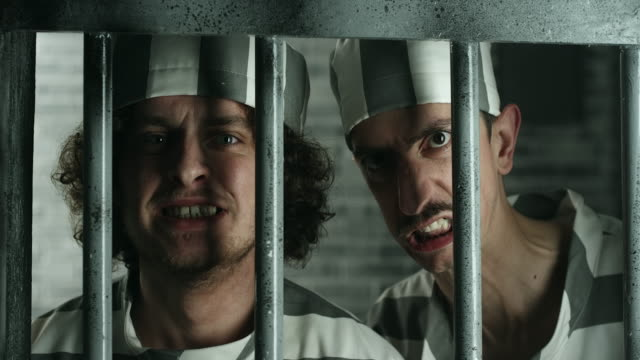 two dangerous prisoners looking through the prison bars - claustrophobia stock videos and b-roll footage