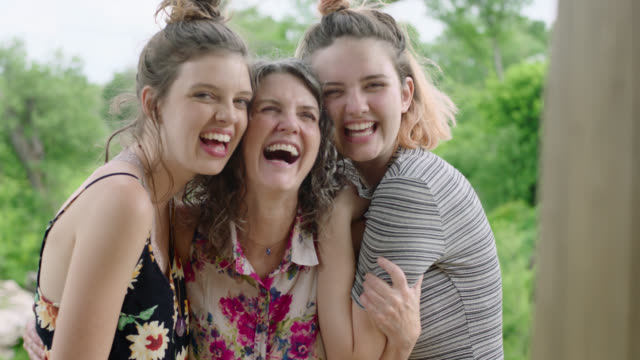 ms slo mo. two daughters hug and kiss their mother and smile and laugh at camera. - daughter stock videos & royalty-free footage