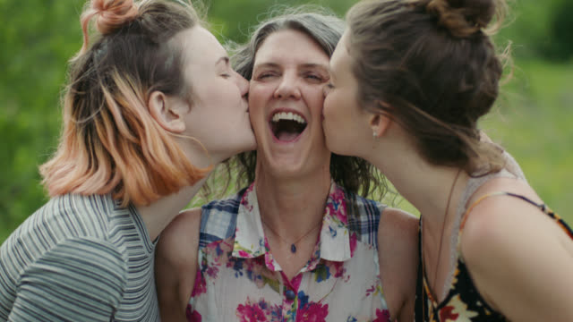 MS SLO MO. Two daughters kiss their mother and laugh together at scenic treetop overlook.