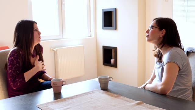stockvideo's en b-roll-footage met twee dove vrienden drinken van koffie en chatten - vertaling