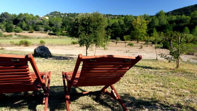 vídeos de stock, filmes e b-roll de duas espreguiçadeiras e espanhol paisagem - cadeira dobrável