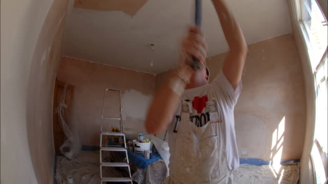Two decorators apply an undercoat of white paint to newly plastered walls