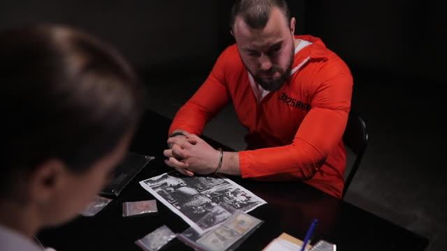 two detectives and male prisoner in interrogation room - prisoner orange stock videos & royalty-free footage