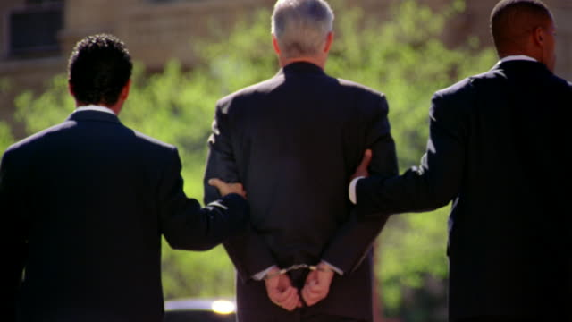 two detectives in suits escort a man with his hands cuffed behind him. - festnahme stock-videos und b-roll-filmmaterial