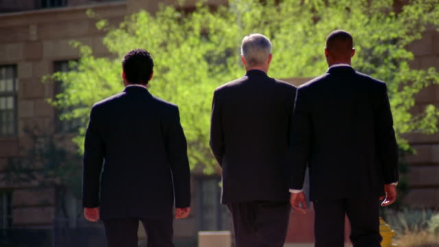 Two detectives in suits escort a middle aged man.
