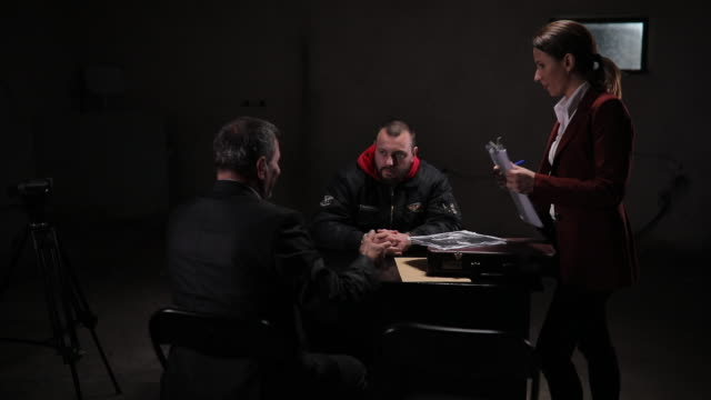Two detectives interrogating a male prisoner