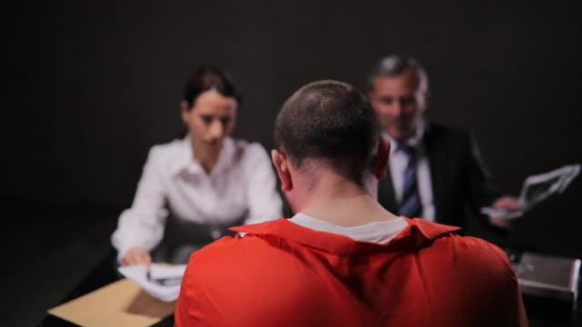 two detectives talking to a prisoner in interrogation room - prisoner orange stock videos & royalty-free footage