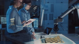 Two Development Engineers are Discussing and Testing an Artificial Intelligence Interface by Playing Chess with a Futuristic Robotic Arm. They are in a High Tech Modern Research Laboratory.