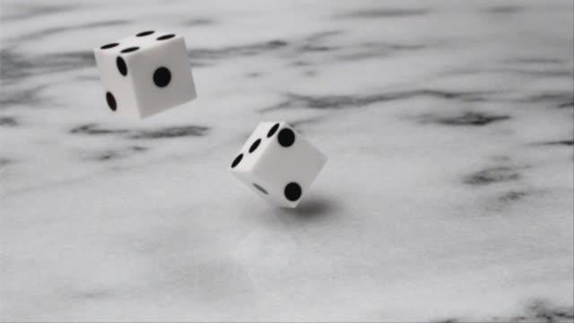 CU SLO MO Two dice rolling sixes / San Francisco, California, USA