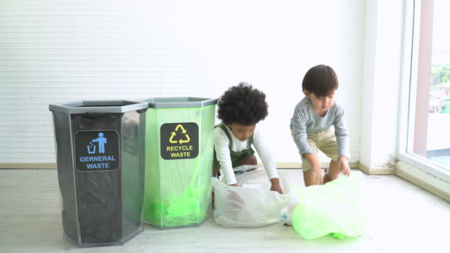 two different ethnic children help to seperate plastic bottle into recyclable bin - decline stock videos & royalty-free footage