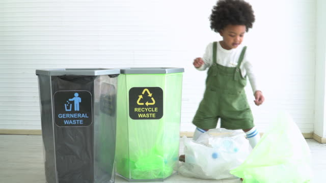 two different ethnic children help to seperate plastic bottle into recyclable bin - responsibility stock videos & royalty-free footage