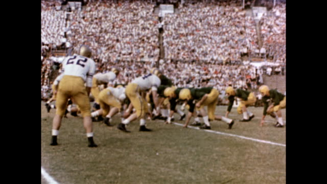 vidéos et rushes de two different football games depicted / cu o f players and coach / players come out of tunnel / large crowd in stadium bleachers / player fouls... - 1954